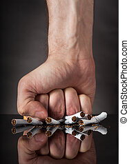 Man's Fist Crushing Cigarettes - Close-up Of Man's Fist...