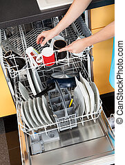 Woman Putting Dishes In The Dishwasher - Happy Woman Putting...