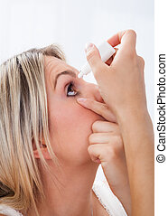 Woman pouring drops in her eyes - Close up young woman...