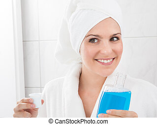 Woman Holding Bottle Of Mouthwash - Young Happy Woman...