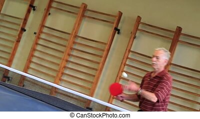 Male - playing table tennis - wide - table tennis - older...