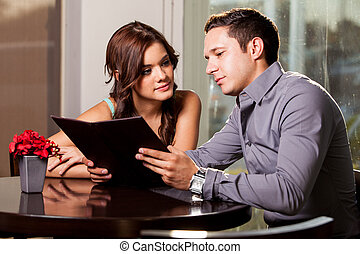 Deciding what to order - Cute young couple looking at a menu...