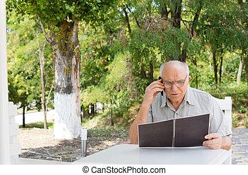 Senior man talking on mobile phone outdoors