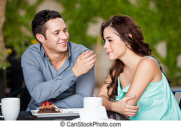 Cute couple sharing cake at a cafe - Happy Hispanic couple...