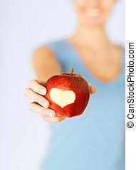 mujer, mano, tenencia, rojo, manzana, corazón, forma