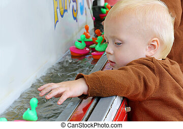 Baby Playing Carnival Duck Game - A baby boy is fishing...