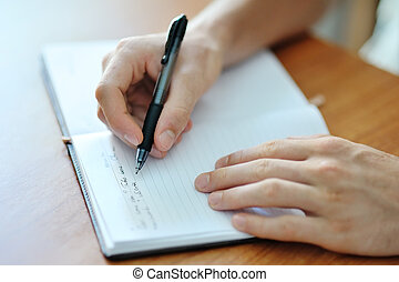 male hand writing on a notebook - male hand with a pen...