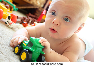 Baby Playing Toys - a cute baby boy with big blue eyes is...