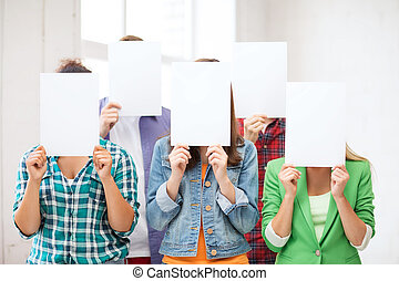students covering faces with blank papers - education...