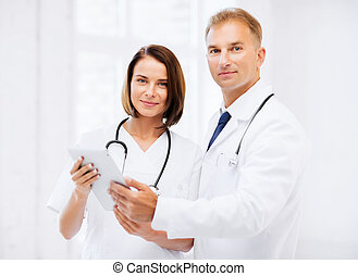 two doctors looking at tablet pc - healthcare and technology...