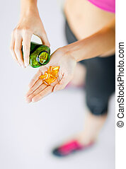 woman hand with capsules - sport and diet concept - woman...