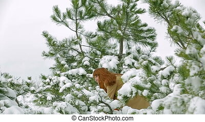 Snowball fight - Woman playing snowball fight in a forest...