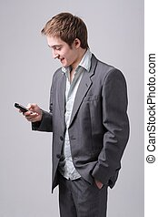 Young man with mobile phone standing against grey background