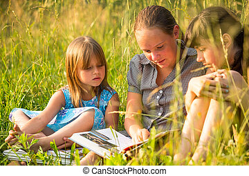 Portrait of three cute little girls reading book in natural environment together.