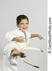 Boy Karate Kick - A young boy jumping and kicking dressed in...