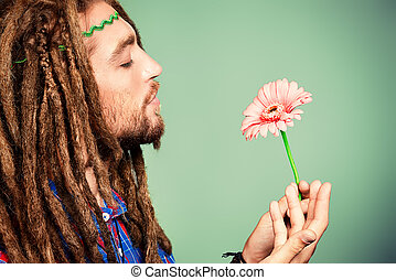 peace symbol - Portrait of a hippie young man with a flower.