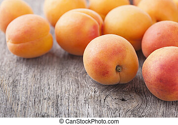 Fresh apricots on wooden background
