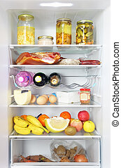 Fridge open full stocked  loaded up with food and fresh ingredients.