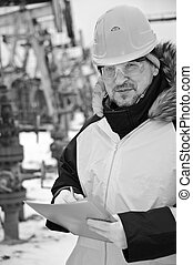 Worker in an Oil field - Engineer in uniform and helmet on...