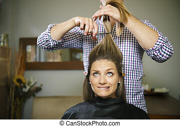 nervous woman in hairdresser shop cutting long hair - female...