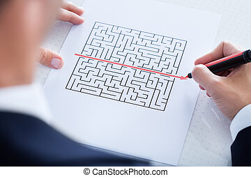 Close-up Of Hand Solving Puzzle - Businessman Solving Maze...