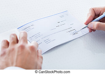 Close-up Of Hand Filling Cheque - A Male Hand Filling Out...