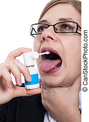 Woman with throat pain using oral spray