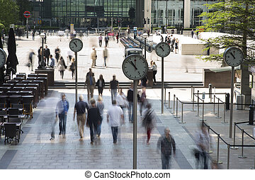 docklands clocks - early morning workers rush past the...