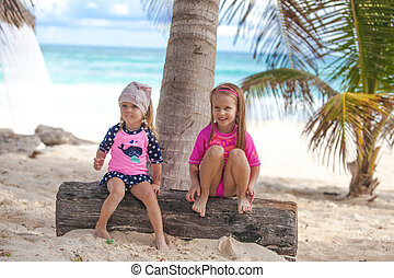 Two little sisters in nice swimsuits have fun at tropical...
