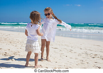 Two little sisters in white clothes have fun at tropical...