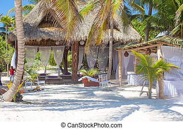 Luxury hotel at tropical resort on ocean shore with palm trees