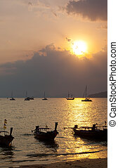 Longtail boats against a sunset. Ao-Nang, Thailand.