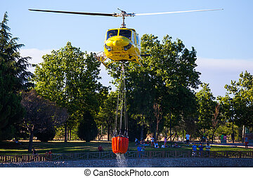 Fire rescue heavy helicopter with water bucket, goes to a...