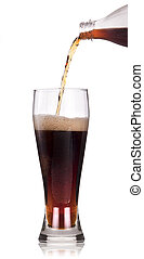 A Bottle of cola soda pouring into a glass over a white...