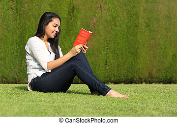 Beautiful arab woman reading a book sitting on the lawn in the park