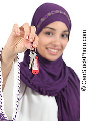 Close up of a beautiful arab woman holding a home keys...