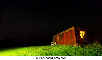 Night time-lapse with a shack and a starry sky