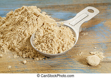 maca root powder - a measuring tablespoon and pile on wooden...