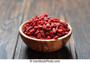 goji berries - wooden bowl with goji berries on the table...