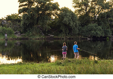 Kids fishing - Boy and girl fishing on a lake