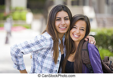 Mixed Race Female Students Carrying Backpacks on School...