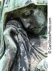 Mourning - detail of a mourning sculpture on a cemetery
