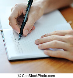 student hand with a pen writing on notebook - male student...