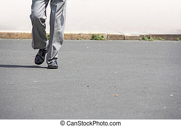 man walking - man in black shoes and gray trousers, walking...