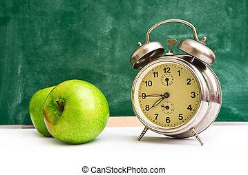 School time again. Clock and apples on teacher's table,...