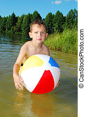the lake a little boy playing with an inflatable ball - In...