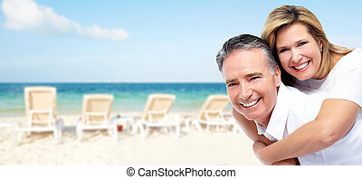 Happy senior couple on a tropical beach Caribbean vacation...
