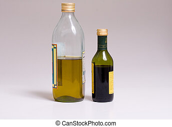 Vinegar and Oil - Bottles of oil and vinegar on a grey...