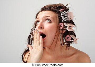 Yawning. Beautiful girl in hair curlers