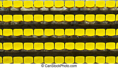 Yellow Bleacher Seats - Yellow bleacher seats in one of the...
